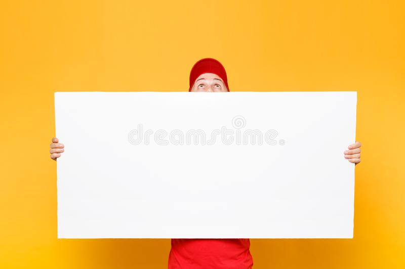 Delivery man in red uniform isolated on yellow orange background. Male employee courier in cap, t-shirt holding big. White empty blank billboard with copy space royalty free stock photos