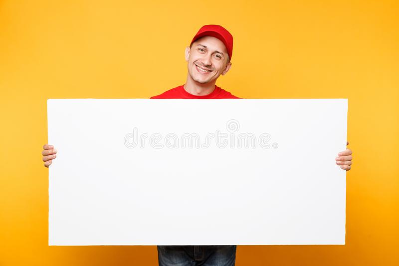 Delivery man in red uniform isolated on yellow orange background. Male employee courier in cap, t-shirt holding big. White empty blank billboard with copy space stock images