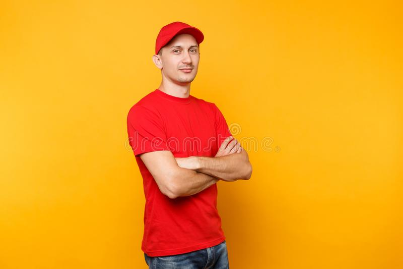 Delivery man in red uniform isolated on yellow orange background. Professional calm confident male employee in cap, t. Shirt courier or dealer holding hands royalty free stock photography