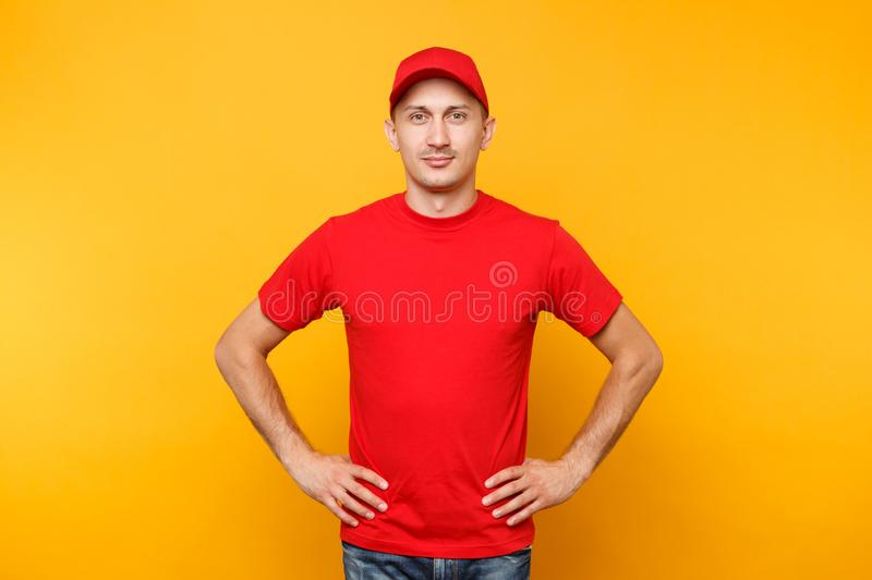 Delivery man in red uniform isolated on yellow orange background. Professional confident male employee in cap, t-shirt. Working as courier dealer standing with stock photos