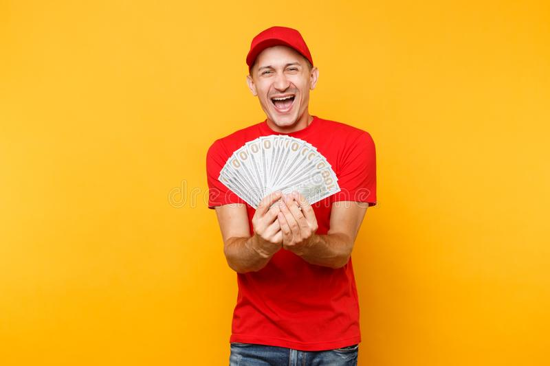 Delivery man in red uniform isolated on yellow orange background. Professional male employee in cap, t-shirt courier or. Dealer holding bundle lots of dollars stock photos