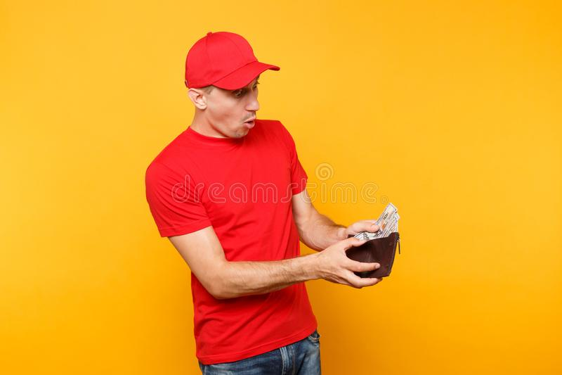 Delivery man in red uniform isolated on yellow orange background. Professional male employee in cap, t-shirt courier or stock photos