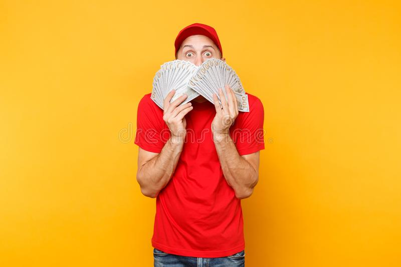 Delivery man in red uniform isolated on yellow orange background. Professional male employee in cap, t-shirt courier or. Dealer holding bundle lots of dollars royalty free stock photo