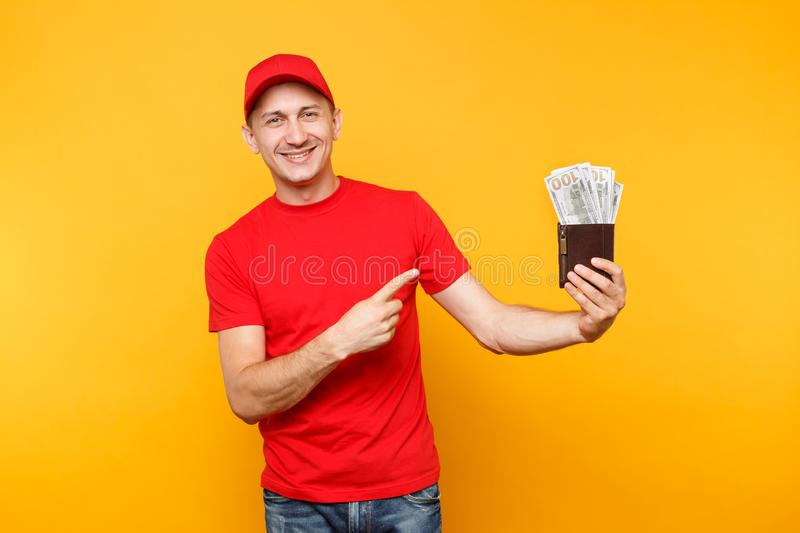 Delivery man in red uniform isolated on yellow orange background. Professional male employee in cap, t-shirt courier or royalty free stock images