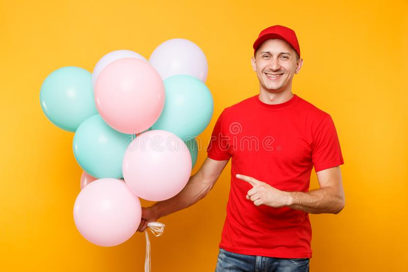 Delivery man in red uniform isolated on yellow orange background. Professional male employee in cap, t-shirt courier. Dealer holding bunch of colorful pastel stock images