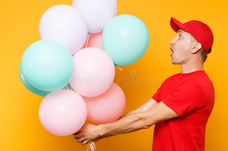 Delivery man in red uniform isolated on yellow orange background. Professional male employee in cap, t-shirt courier. Dealer holding bunch of colorful pastel royalty free stock image