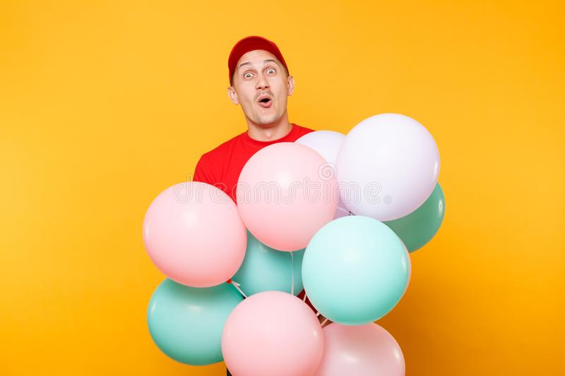 Delivery man in red uniform isolated on yellow orange background. Professional male employee in cap, t-shirt courier. Dealer holding bunch of colorful pastel stock image