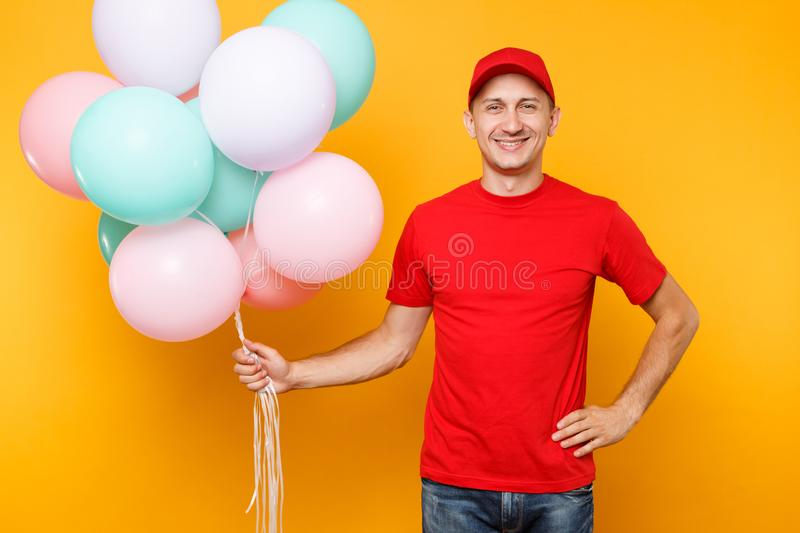 Delivery man in red uniform isolated on yellow orange background. Professional male employee in cap, t-shirt courier. Dealer holding bunch of colorful pastel stock photography