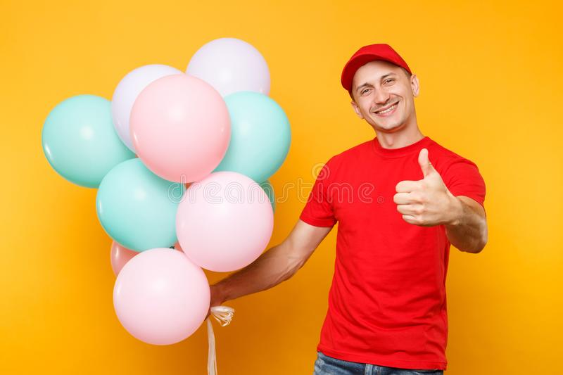 Delivery man in red uniform isolated on yellow orange background. Professional male employee in cap, t-shirt courier. Dealer holding bunch of colorful pastel royalty free stock photo