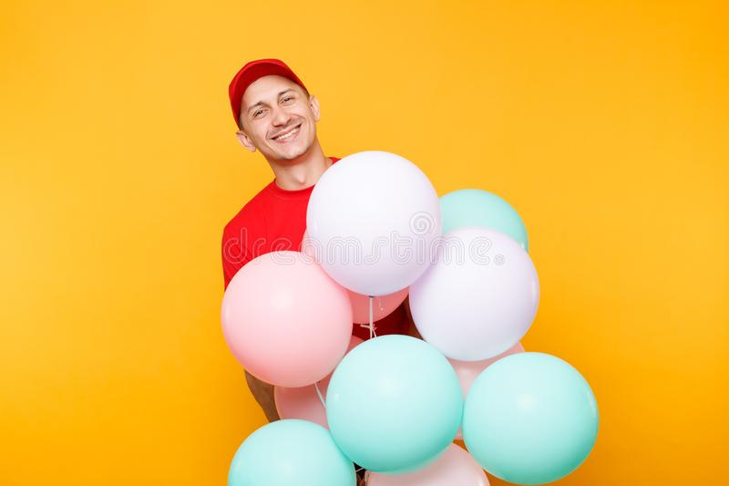 Delivery man in red uniform isolated on yellow orange background. Professional male employee in cap, t-shirt courier. Dealer holding bunch of colorful pastel royalty free stock photos