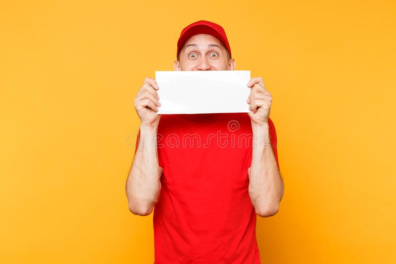 Delivery man in red uniform isolated on yellow orange background. Professional male employee courier in cap, t-shirt. Hold white empty blank paper. Service stock photos