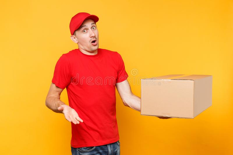 Delivery man in red uniform isolated on yellow orange background. Confused sad male employee courier or dealer in cap t royalty free stock image