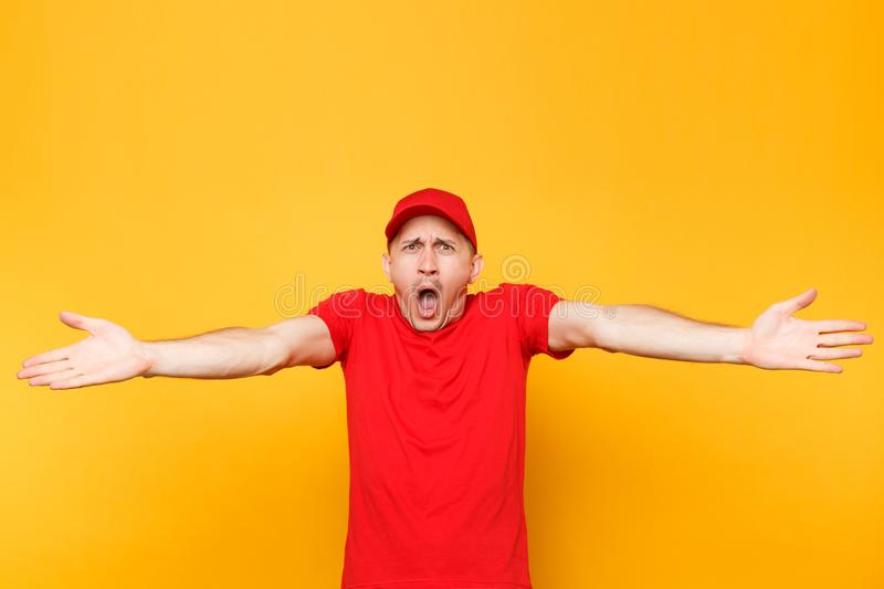 Delivery man in red uniform isolated on yellow orange background. Professional perturbed shocked male employee in cap, t. Shirt working as courier dealer royalty free stock photo