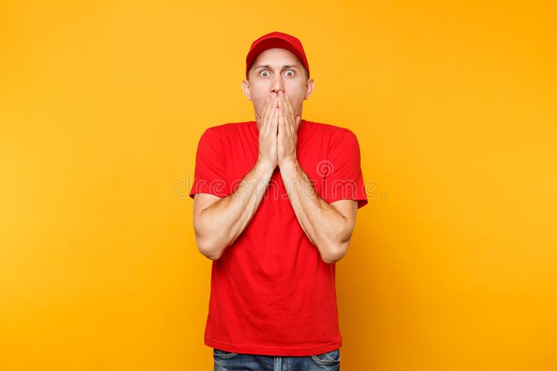 Delivery man in red uniform isolated on yellow orange background. Professional shocked male employee in cap, t-shirt. Working as courier or dealer cover mouth royalty free stock images