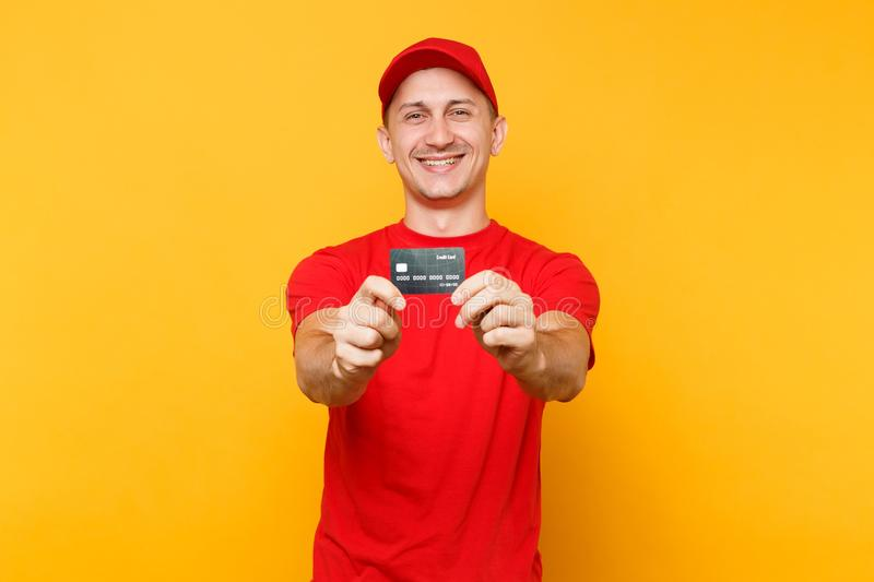 Delivery man in red uniform isolated on yellow orange background. Professional smiling male employee in cap, empty t. Shirt courier or dealer hold in hand stock photo