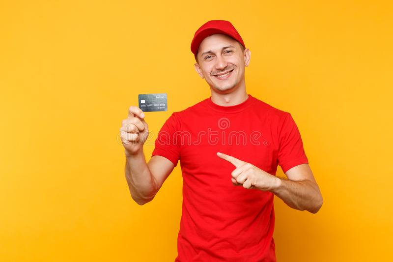 Delivery man in red uniform isolated on yellow orange background. Professional smiling male employee in cap, empty t. Shirt courier or dealer hold in hand royalty free stock photos