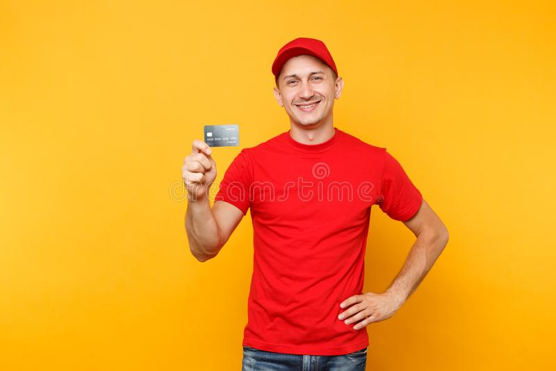 Delivery man in red uniform isolated on yellow orange background. Professional smiling male employee in cap, empty t. Shirt courier or dealer hold in hand royalty free stock images