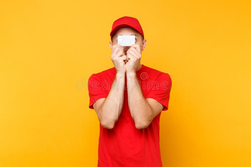 Delivery man in red uniform isolated on yellow orange background. Professional male employee in cap, empty t-shirt. Delivery man in red uniform isolated on royalty free stock image