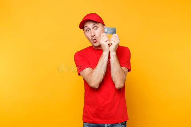 Delivery man in red uniform isolated on yellow orange background. Professional smiling male employee in cap, empty t. Shirt courier or dealer hold in hand stock photos