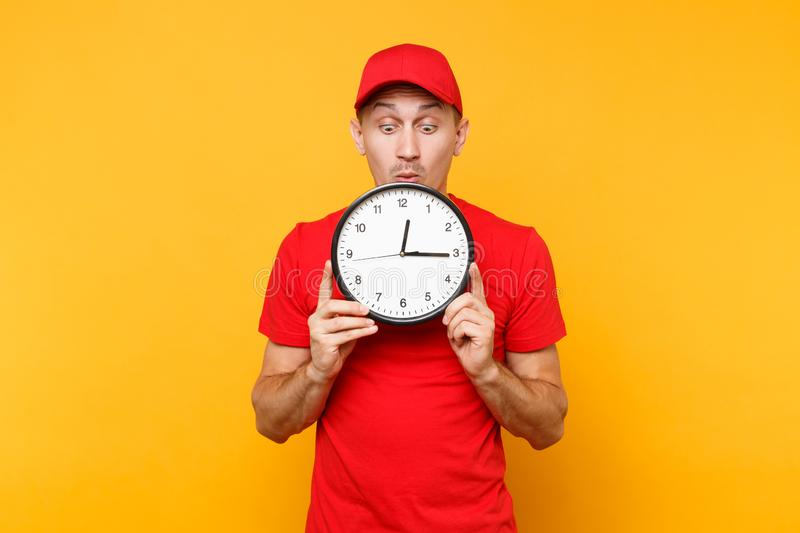 Delivery man in red uniform isolated on yellow orange background. Professional smiling male employee in cap, empty t. Shirt working as courier or dealer holding stock photography