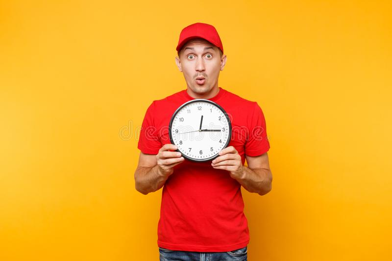 Delivery man in red uniform isolated on yellow orange background. Professional smiling male employee in cap, empty t. Shirt working as courier or dealer holding stock photos