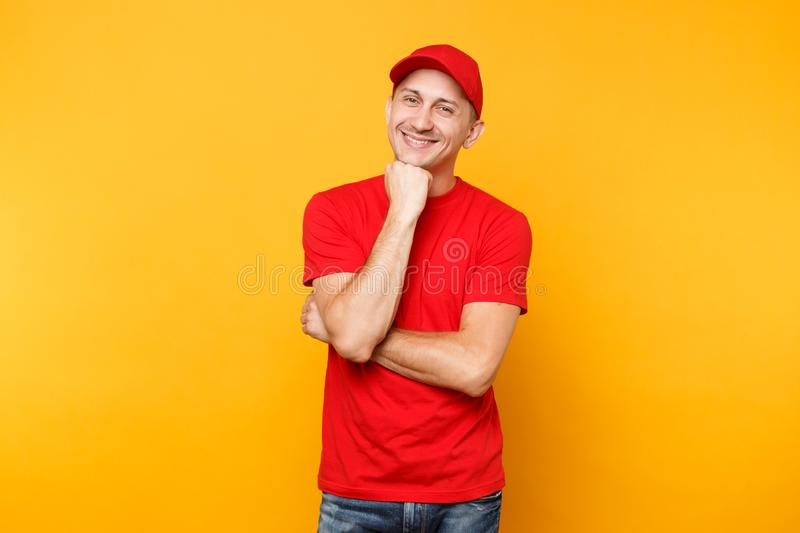 Delivery man in red uniform isolated on yellow orange background. Professional smiling male employee in cap, t-shirt. Working as courier or dealer put hand prop stock photo