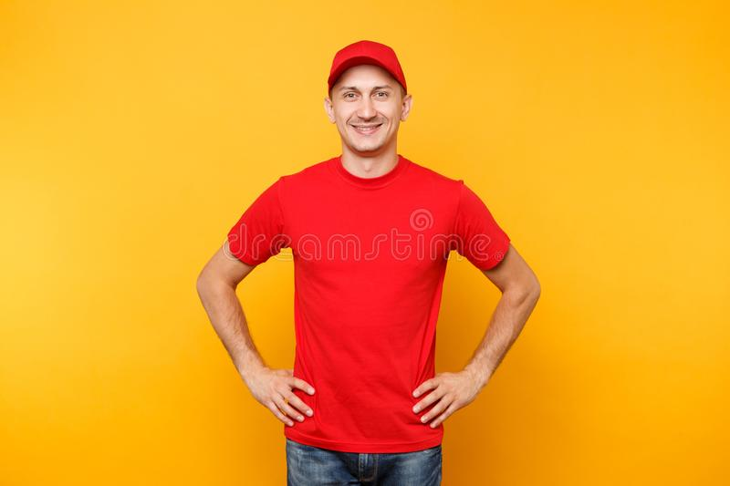 Delivery man in red uniform isolated on yellow orange background. Professional smiling male employee in cap, t-shirt. Working as courier or dealer standing with royalty free stock image