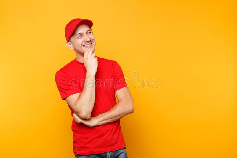 Delivery man in red uniform isolated on yellow orange background. Professional smiling male employee in cap, t-shirt. Working as courier or dealer put hand prop stock photos