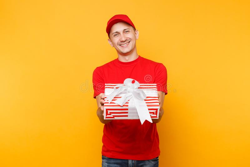 Delivery man in red uniform isolated on yellow orange background. Professional smiling male employee in cap, t-shirt. Working as courier or dealer holding red stock photography