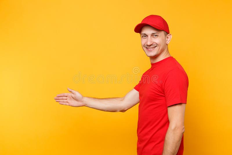 Delivery man in red uniform isolated on yellow orange background. Side view smiling male employee in cap, t-shirt. Courier dealer standing with outstretched stock images