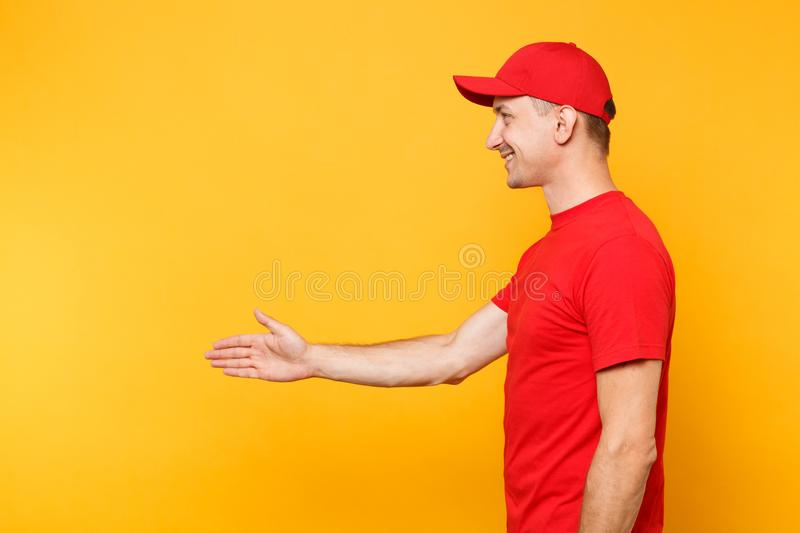 Delivery man in red uniform isolated on yellow orange background. Side view smiling male employee in cap, t-shirt stock images