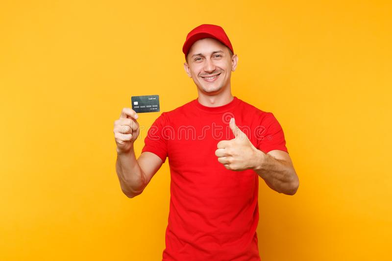 Delivery man in red uniform isolated on yellow orange background. Smiling male employee in cap, empty t-shirt courier. Holding in hand credit bank card, showing royalty free stock images