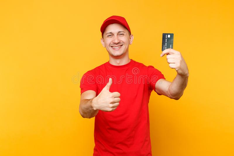 Delivery man in red uniform isolated on yellow orange background. Smiling male employee in cap, empty t-shirt courier. Holding in hand credit bank card, showing royalty free stock photography