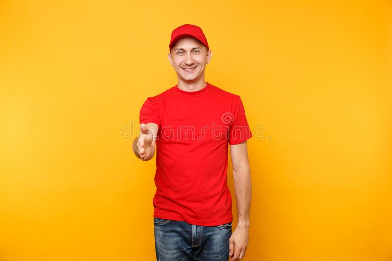 Delivery man in red uniform isolated on yellow orange background. Smiling male employee in cap, t-shirt working as. Courier dealer standing with outstretched royalty free stock images