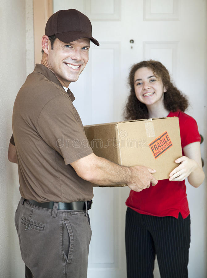 Delivery Man and Satisfied Customer. Handsome delivery man smiles as he delivers a package to a customer royalty free stock images