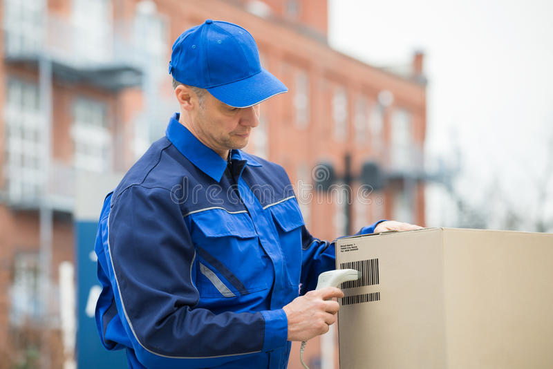 Delivery Man Scanning Cardboard Boxes With Barcode Scanner. Delivery Man Standing And Scanning Cardboard Boxes With Barcode Scanner royalty free stock photos