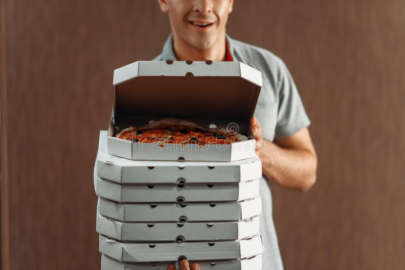 Delivery man shows fresh pizza, delivering service. Delivery man shows fresh pizza in box, delivering service. Courier from pizzeria holds cardboard packages royalty free stock photos