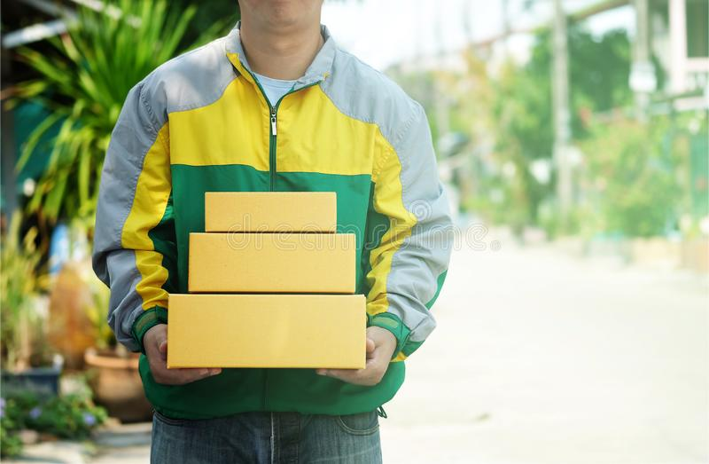 Delivery man staff in the colorful jacket uniform holds parcel box that is about to be delivered to customer. With blurred background, with copy space royalty free stock images