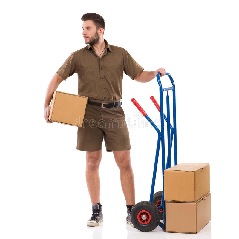 Delivery Man Is Standing Close To Push Cart And Looking Away. Male courier is standing close to push cart, holding package under his arm and looking away. Full stock image