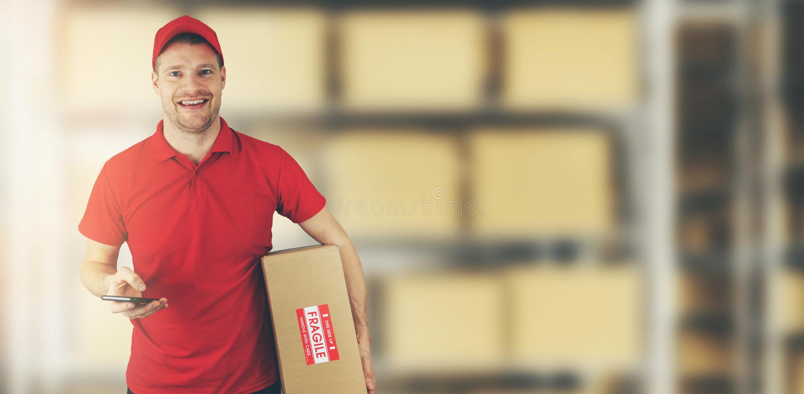 Delivery man standing in warehouse holding cardboard box and mobile phone stock photography