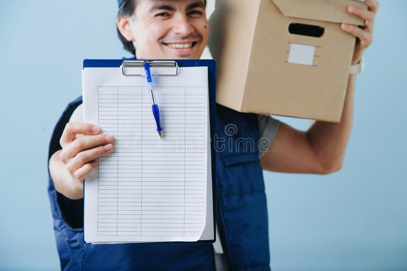 Delivery man in uniform is holding parcel cardboard box over blue background. royalty free stock images