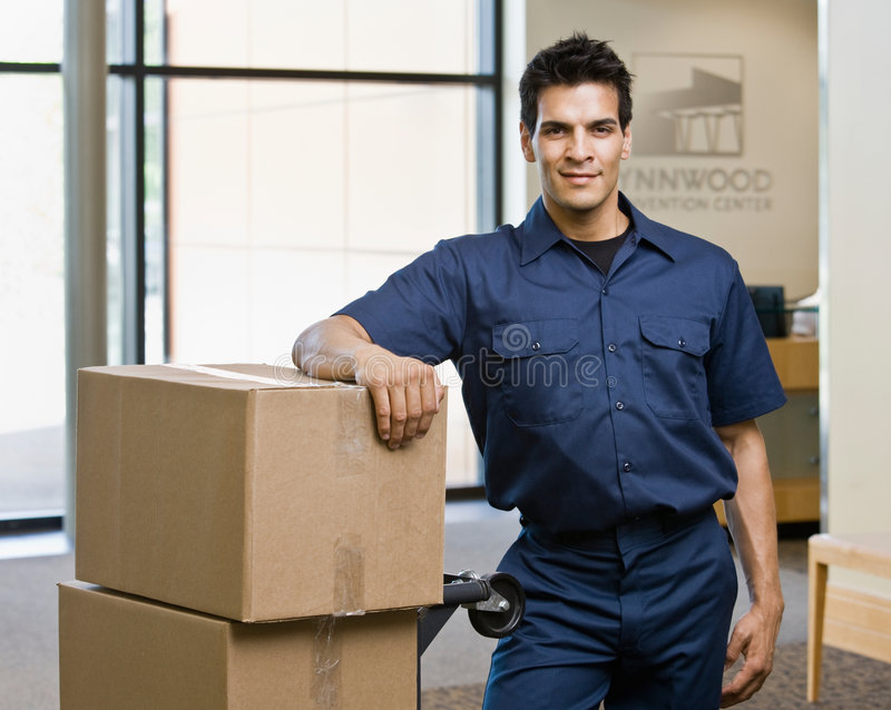 Delivery man in uniform posing with stack of boxes stock images