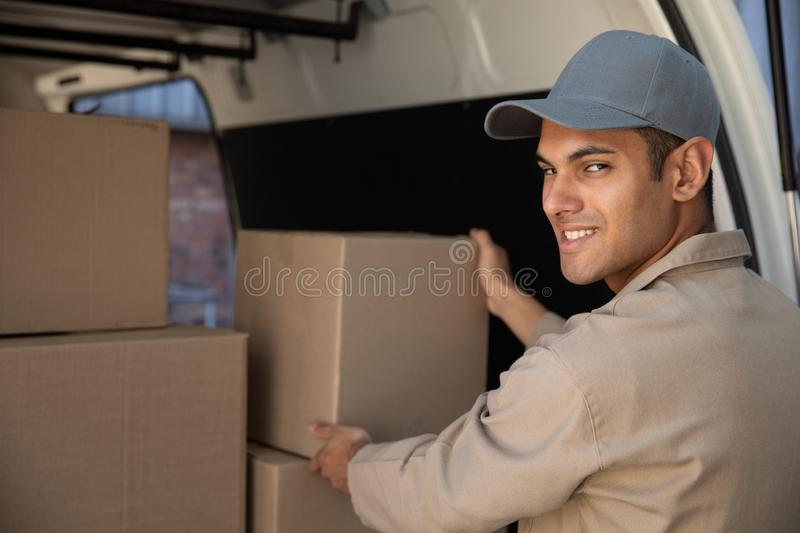 Delivery man unloading cardboard boxes from a van outside the warehouse royalty free stock photos
