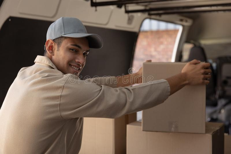 Delivery man unloading cardboard boxes from a van outside the warehouse stock photography