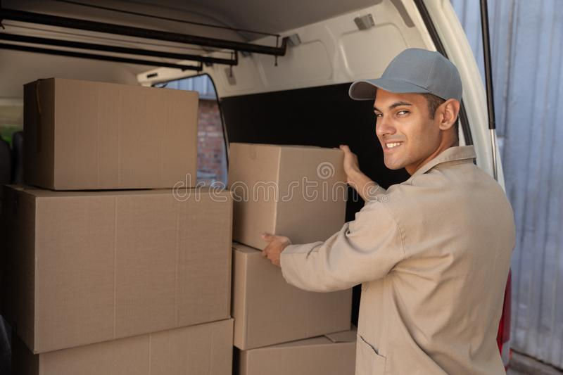 Delivery man unloading cardboard boxes from a van outside the warehouse stock photo