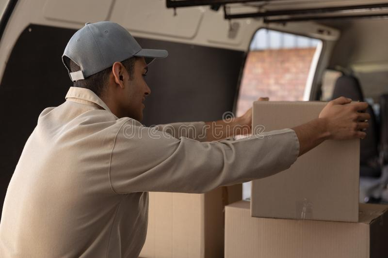 Delivery man unloading cardboard boxes from a van outside the warehouse stock images