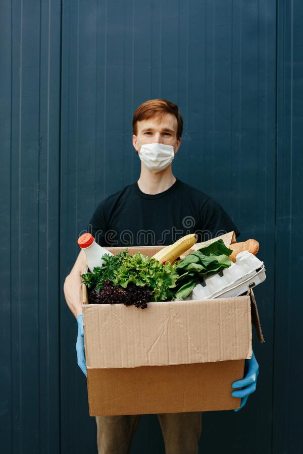 Delivery Man Wearing Medical Mask And Gloves Holding Box in Hands on dark background. Delivery services courier during the royalty free stock photos