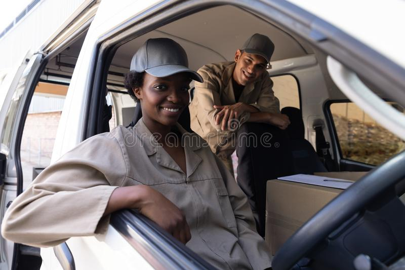 Delivery man and woman looking at camera while sitting in van outside the warehouse. Happy delivery man and woman looking at camera while sitting in van outside royalty free stock photo