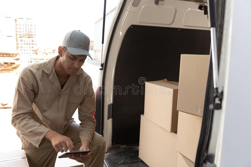 Delivery man working on laptop near van outside the warehouse. Front view of delivery man working on laptop near van outside the warehouse. This is a freight stock image