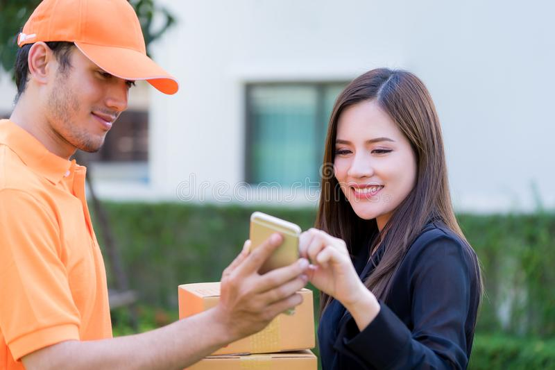 Delivery man asking for signature for package delivery. Delivery men is asking for signature for package delivery royalty free stock images